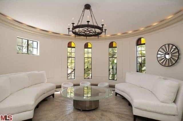 The white curved walls follow the lay of the round white ceiling with a farmhouse-style chandelier hanging in the middle over the round glass-top coffee table flanked by a couple white curved sofas.