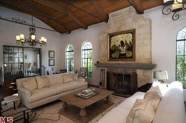 The beautiful classical painting mounted above the fireplace is a nice accent to the living room that has a couple of comfortable couches flanking a wooden coffee table all under a wooden ceiling with exposed wooden beams.