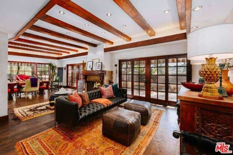 The white ceiling of this bright living room is dominated by exposed wooden beams that match the orange patterned area rug over the dark hardwood flooring that is complemented by the black leather tufted couch paired a couple of leather ottomans.