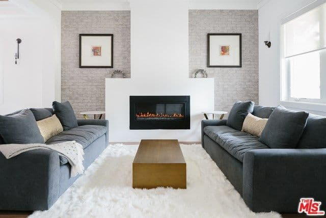 This living room has a nice modern symmetry to its simple white mantle of the modern fireplace flanked with a couple of light hued brick walls adorned with framed artworks facing two navy blue velvet couches on either side of the simple wooden coffee table.