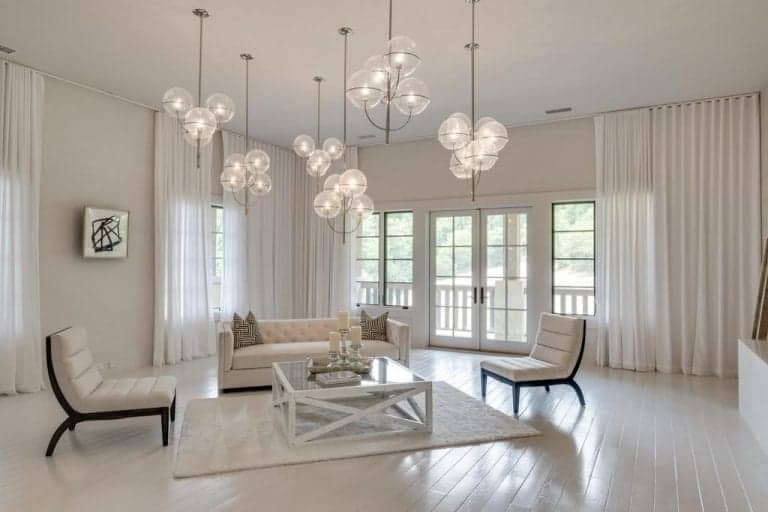 The white walls and ceiling of this spacious living room is dominated by multiple spherical pendant lights that has frosted glass hanging over the glass-top white wooden coffee table surrounded by a white couch and two white cushioned chairs.