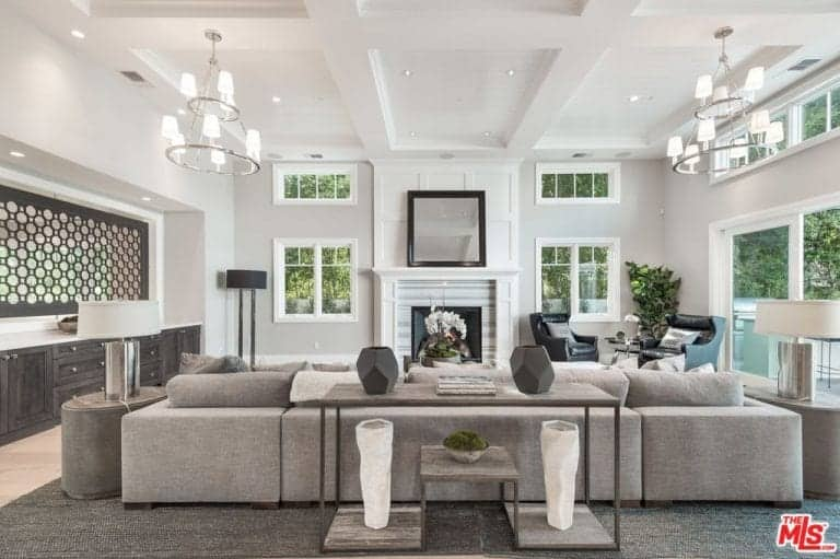 This living room has a high white coffered ceiling adorned with a couple of white chandeliers over the large gray sectional sofa facing a fireplace with a white mantle flanked with windows.