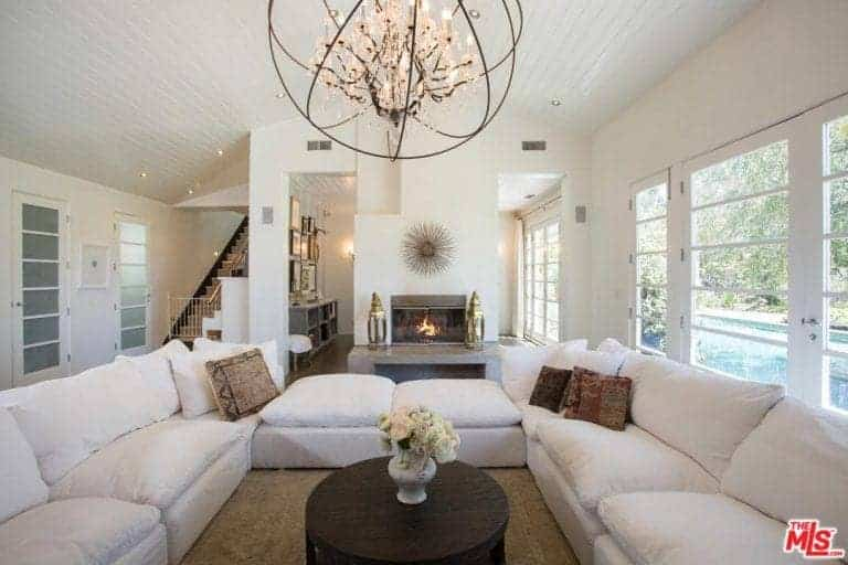 This bright living room has a high cathedral ceiling that supports a large chandelier with a spherical design hanging over the circular wooden table that is surrounded by a white U-shaped sectional sofa over a brown woven area rug.