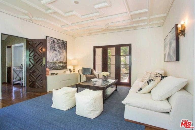 The white patterned ceiling is paired with a dark hardwood flooring that is mostly covered with a blue woven area rug that contrasts the white comfortable sofa facing a dark wooden coffee table.