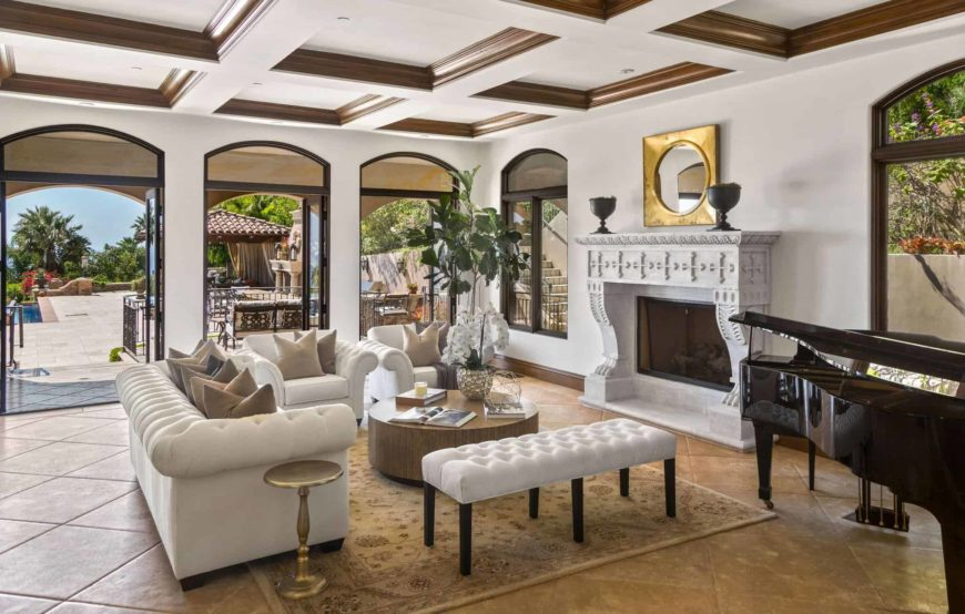 The fireplace has an elegant carved mantle made of white stone that matches with the brilliant white coffered ceiling with wooden details that match the circular wooden coffee table of the white sofa set over the beige flooring tiles.