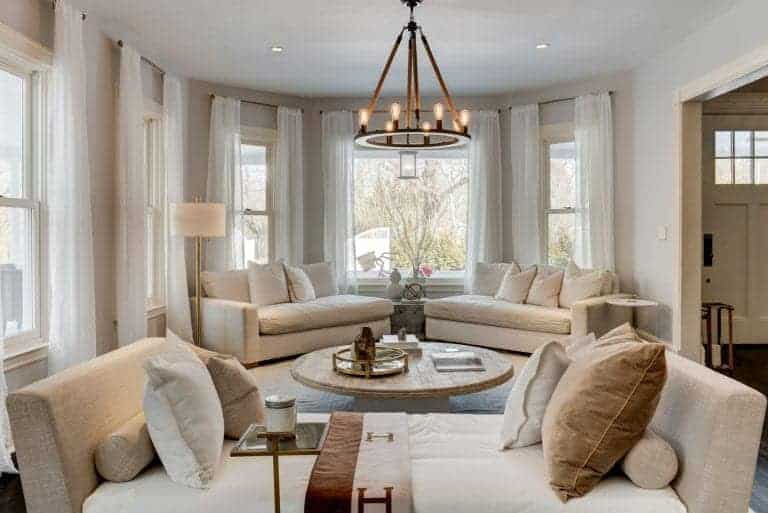 This bright living room is augmented by the natural lights coming in from the surrounding windows that have white curtains complementing the beige couches surrounding the round wooden coffee table.