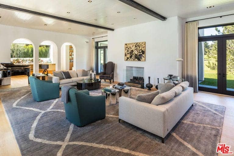 The white ceiling is accented with a couple of exposed dark wood beams matching the dark frames of the glass doors flanking the white wall housing a fireplace and an abstract painting facing two gray sofas and two green cushioned armchairs.