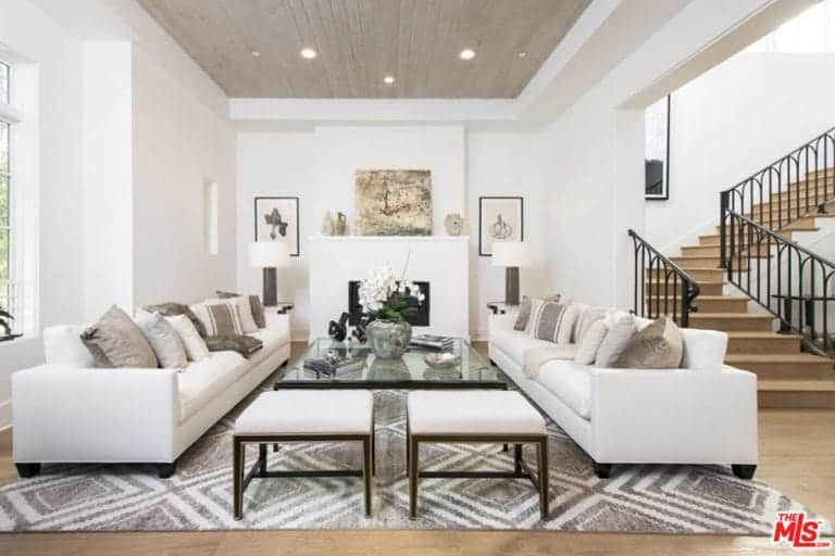 The white tray ceiling has a gray center tray that matches with the light gray patterned area rug under the pair of long white leather sofas flanking a glass-top coffee table across from the white fireplace adorned with paintings and decors.