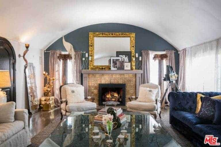 This living room is filled to the brim with elegant details and different hues like the velvet blue sofa facing a glass-top coffee table across from the beige stone mantle of the fireplace.