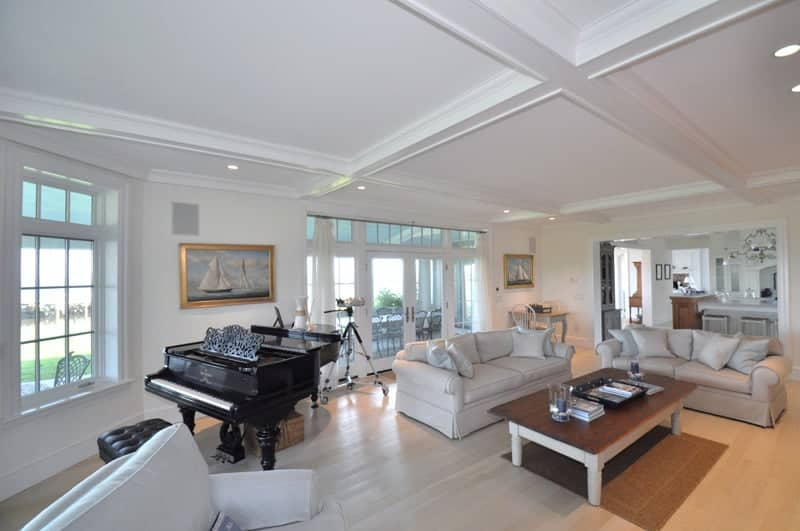 This is an elegant and luxurious living room augmented with a black grand piano that stands out against the light hardwood flooring that complements the white comfortable sofas facing the wooden coffee table topped with a white coffered ceiling.