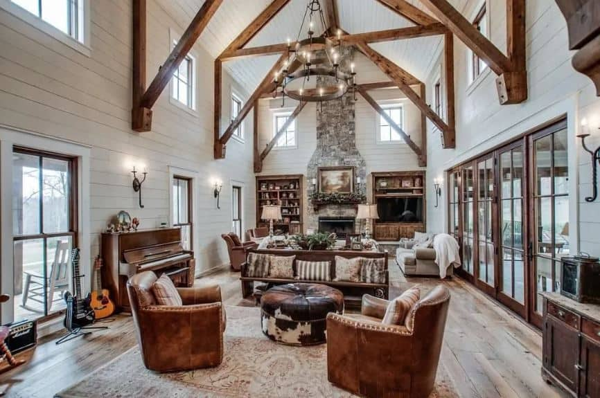 This is a large and comfortable high-ceiling living room filled with rustic and farmhouse elements that elevate the homey comfort it exudes. The massive two-tier farmhouse-style chandelier matches with the brown wooden elements of the rest of the living room.
