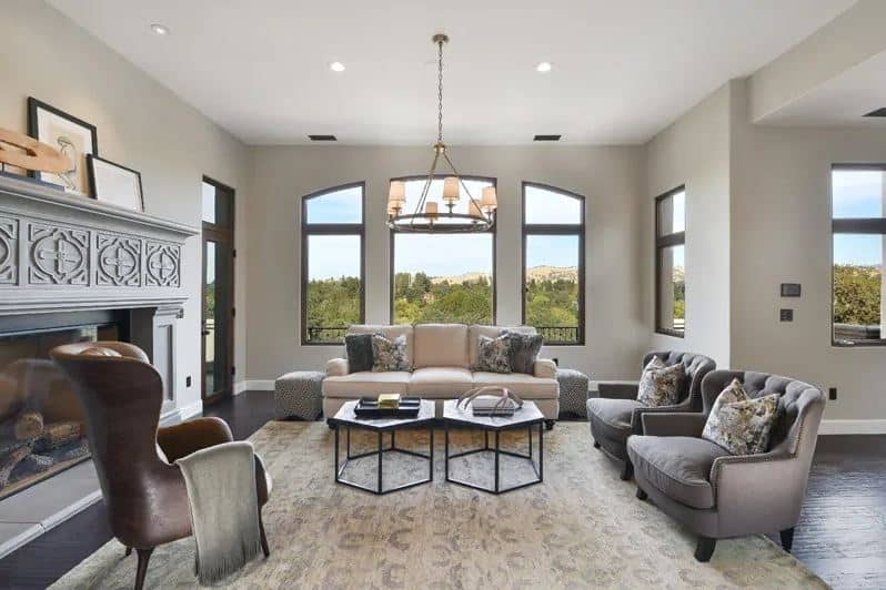 This simple living room has a brightness to it that comes from the abundance of natural light coming in from the arched windows complemented by a beige couch and a couple of hexagonal coffee tables above a beige area rug.