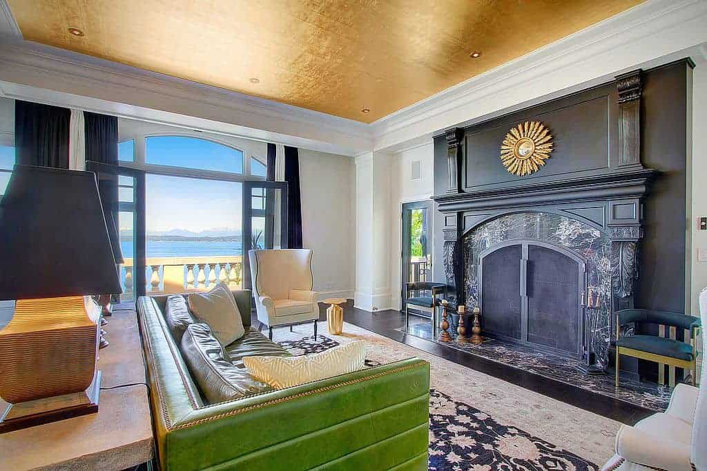 This eclectic living room has a gold ceiling that matches with the golden sun-like decor mounted above the black mantle of the fireplace as well as the gold trim lining the edges of the green leather couch.