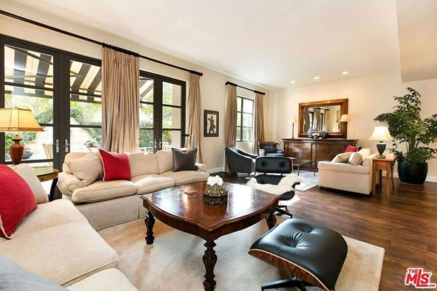 The dark wood coffee table matches with the dark hardwood flooring that contrasts the beige walls and ceiling that are brightened by the glass doors and windows. This is complemented by the beige sofa set and beige curtains.