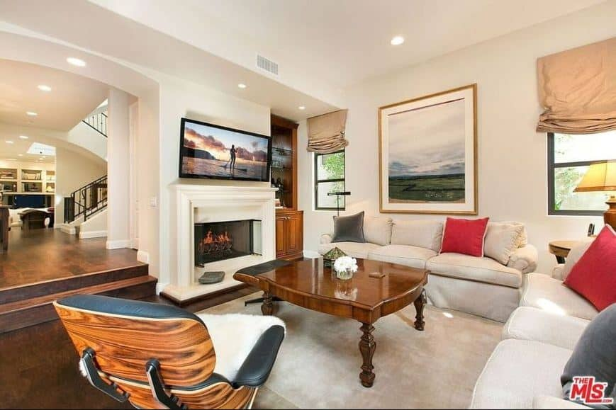 The fireplace has a white mantle topped with a wall-mounted TV that pairs well with the large painting mounted over the light gray sofa with a round side table bearing a warm yellow lamp that complements the dark hardwood flooring.