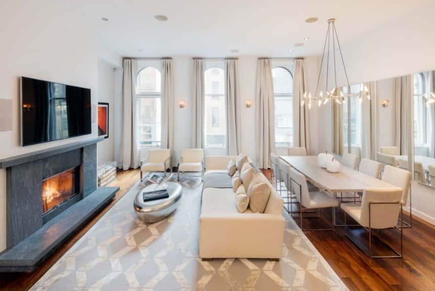 This is a white high-ceiling grand room that houses both the dining area and the living room that is marked with a light gray patterned area rug that complements the large beige sofa facing a gorgeous fireplace inlaid with gray marble.