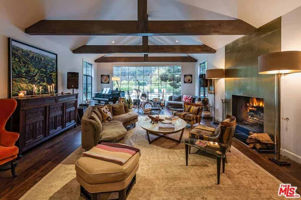 This comfortable living room has a cathedral ceiling paired with large wooden beams that matches the hardwood flooring that is mostly covered with a beige area rug. The stand-out element here is the fireplace housed in a golden panel of the wall.