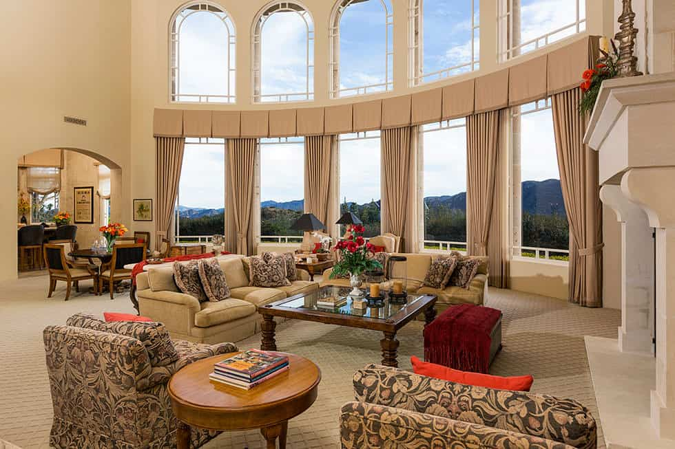 This luxurious and spacious beige living room is accented with tall arched windows that dominate the high curved walls that matches the beige carpeted flooring and contrasted by floral patterned cushioned armchairs and pillows.