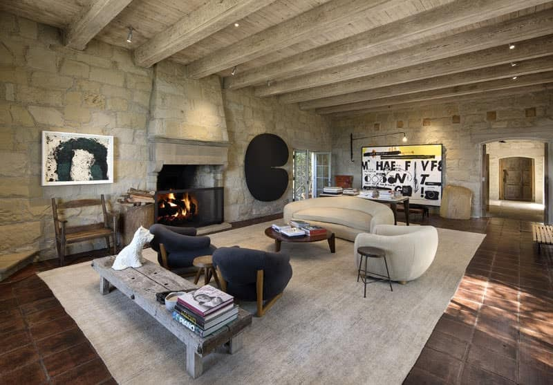 The rough stone walls are a nice complement to the wooden ceiling with exposed wooden beams and the terracotta floor tiles topped with a light gray area rug matching the modern curved sofa set facing the fireplace.