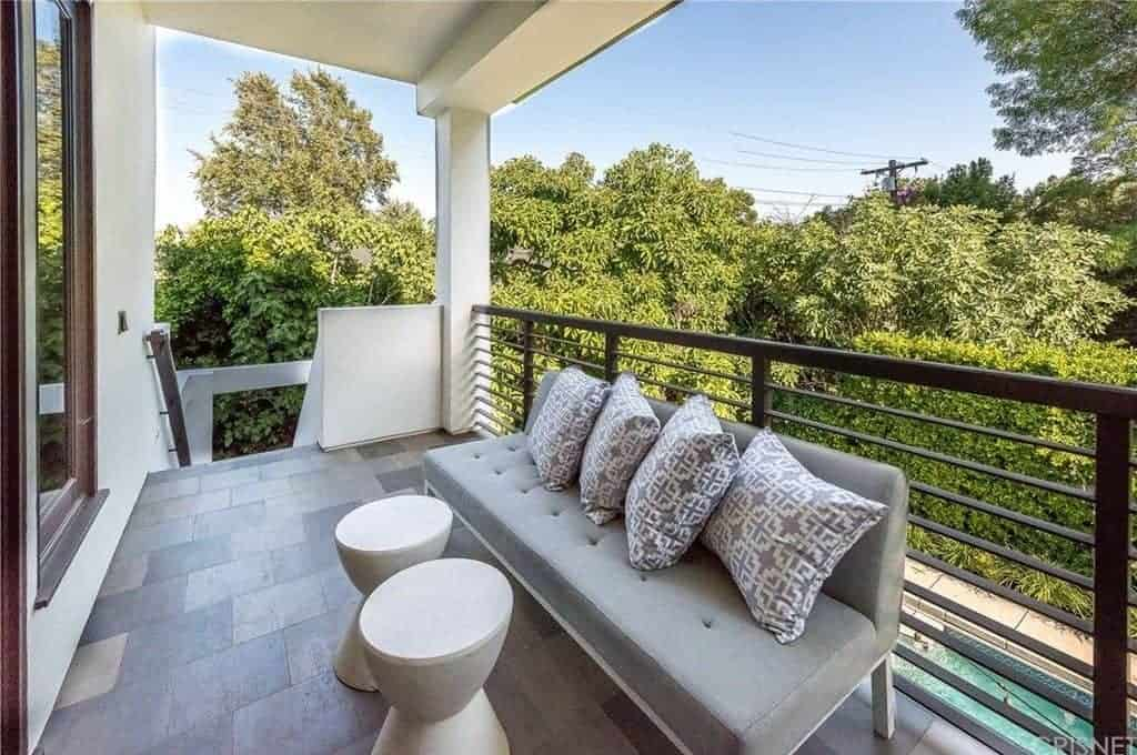 This small balcony patio has a gray cushioned couch backed against the wrought iron railings that feature a lush green background filled with treetops. This couch is paired with a couple of white stools that can also work as tables.