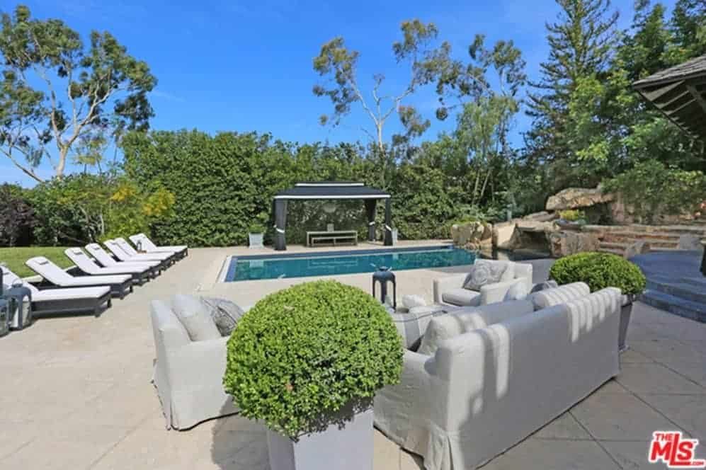 The large swimming pool is surrounded by multiple white lounge chairs on one side and in the other is a lovely sitting area with a white cushioned couch flanked by potted plants over a beige flooring of large outdoor tiles.