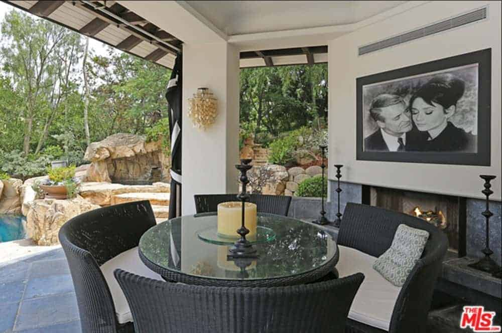 This is an outdoor dining area by an outdoor fireplace that is inlaid with the same gray stone as the flooring. It is topped with a beige wall adorned with a large classic photograph looking over the round glass-top woven wicker table and its matching chairs.