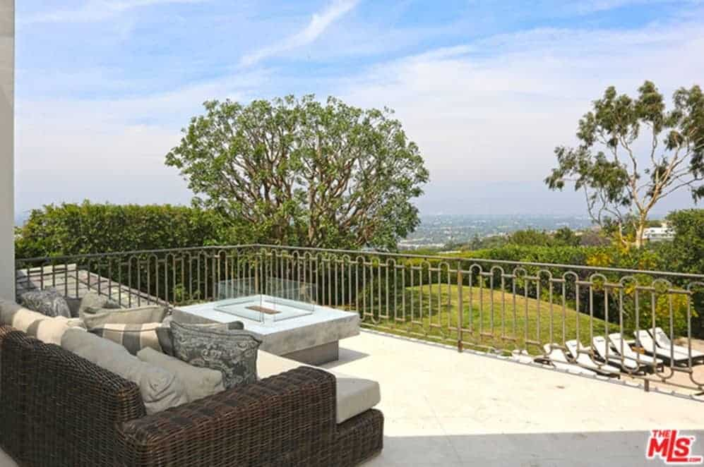 This balcony patio has a woven rattan sectional sofa filled with comfortable cushions and patterned pillows. The comfort and warmth of this area is augmented by the modern firepit near the iron railings that offer a nice view.
