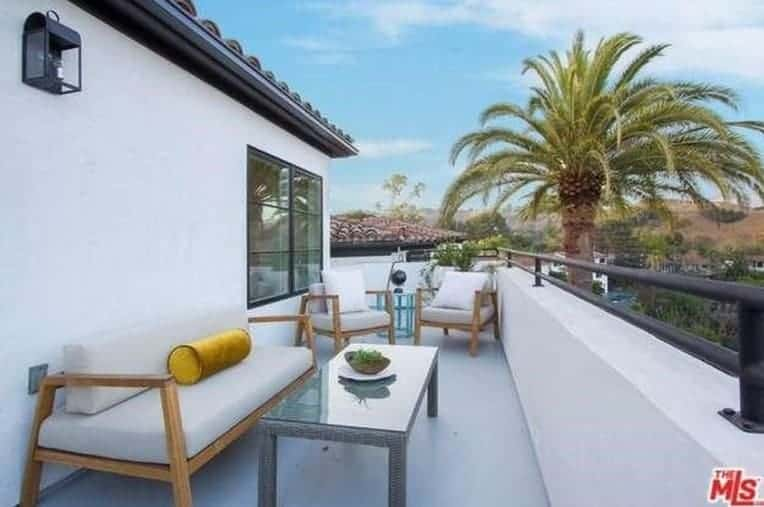 The side of the house exterior offers a white background for the matching light gray cushions of the wooden armchairs and bench facing a glass-top woven wicker coffee table complemented by a large palm tree on the side.