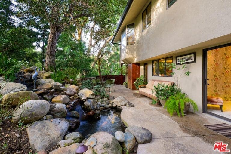 This backyard has a spectacular landscaping that melds with the surrounding forest of tall trees. There is a comfortable woven wicker bench with beige cushions for those who want to enjoy looking at the stream-like landscaping filled with large stones.