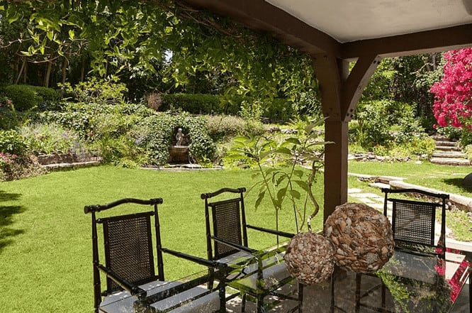 This patio has a wooden ceiling supported by dark brown wooden beams and pillars adorned with a blanket of plants hanging over the side matching with the background of manicured lawn and lush garden with colorful flowers and stone walkways.