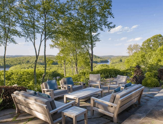There is a great river view filled with trees topped with a blue sky that serves as a serene background for this outdoor patio with wooden benches and armchairs surrounding a rectangular wooden coffee table over a stone flooring.