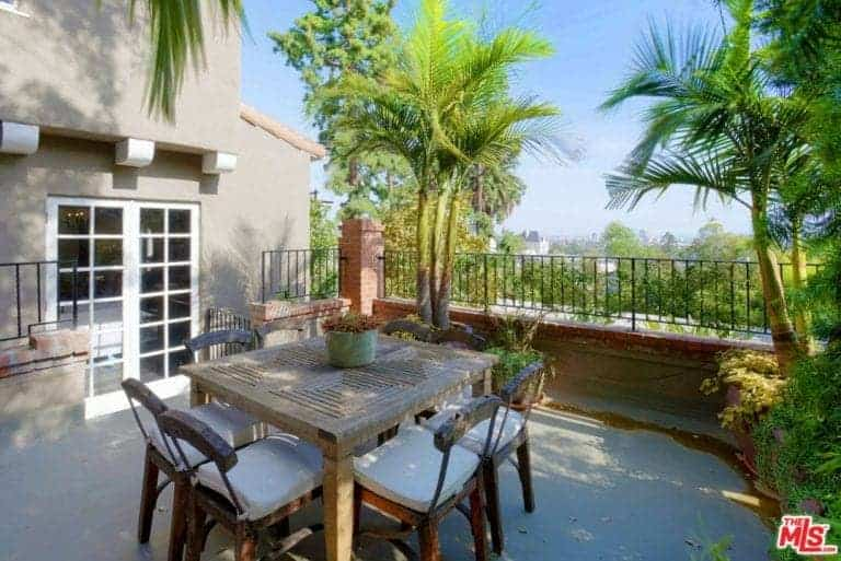 This wonderful outdoor patio has a wooden square table surrounded by wooden chairs with white cushions given a nice background of small palm trees planted on the sides of the wrought iron railings of the red brick balcony.