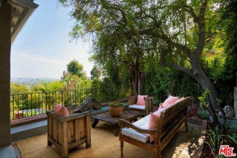 This beautiful balcony patio has a lush mini garden with trees and shrubs on two adjacent sides of the wooden outdoor sitting area paired with a low wooden coffee table topped with a potted plant over a brown woven area rug.