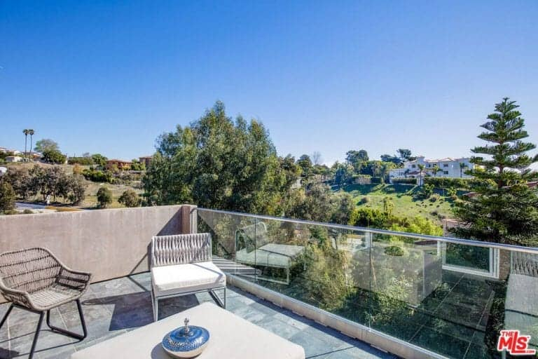 This balcony patio offers a nice overlooking view of a neighborhood filled with tall trees and greenery augmented by a glass panel for a maximum viewing experience to those sitting on the woven rattan chairs by a beige coffee table.