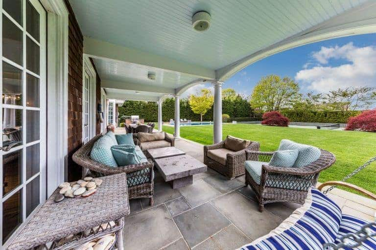 The large terracotta tiles of the flooring goes well with the multiple support pillars of the white ceiling that has flush mount lighting over the woven rattan sofa and armchairs with green patterned cushions matching the green lawn of the backyard.
