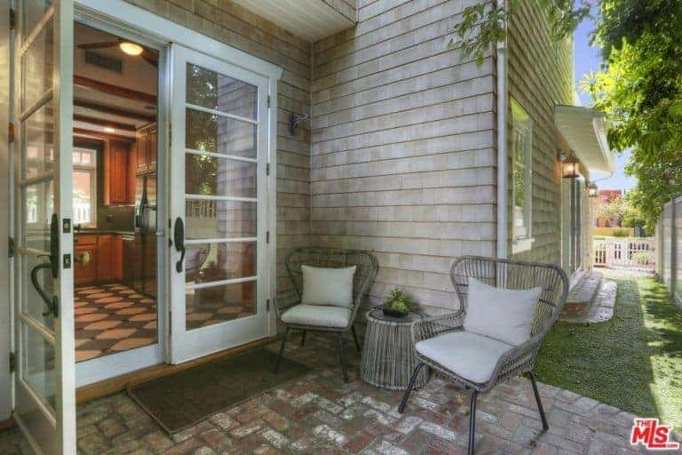 The pair of light gray woven wicker armchairs have light gray cushions for a comfortable relaxation area by the side of the house just outside the white glass doors contrasting the red brick flooring.