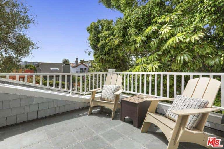 This balcony patio features a lush green background from the tall trees surrounding the house. This provides a nice contrast for the white balcony railing complemented by the pair of bare wooden lounge chairs flanking a small wooden side table.