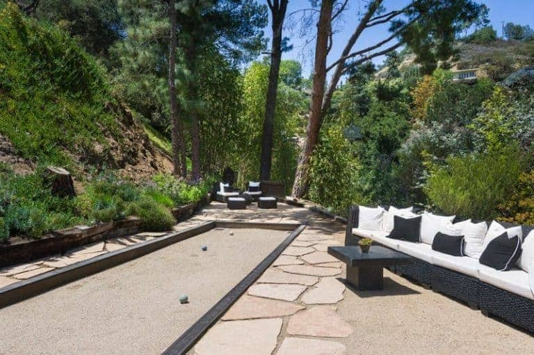 This brilliant outdoor patio makes the most of the amazing and lush landscape of trees and bushes which serves as a nice background for the black woven wicker seats that is contrasted by the white cushions paired with a small black wooden coffee table.