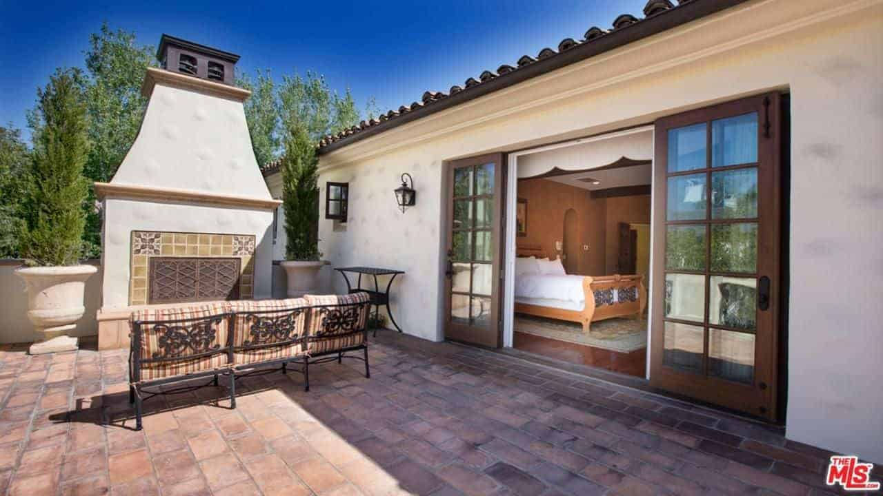 The terracotta flooring of this outdoor patio is a perfect match for the outdoor fireplace inlaid in a large white structure leading to a black chimney above. This is best enjoyed with the cushioned wrought iron bench facing it.