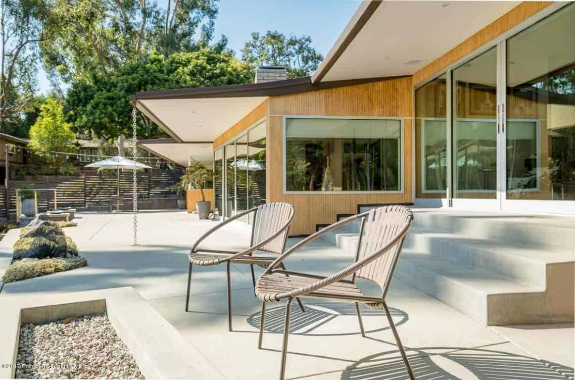 This is a simple backyard patio that has a couple of outdoor chairs facing a firepit inlaid with concrete the same as the floor adorned with a small patch of greenery that has decorative stones and moss-like plants.