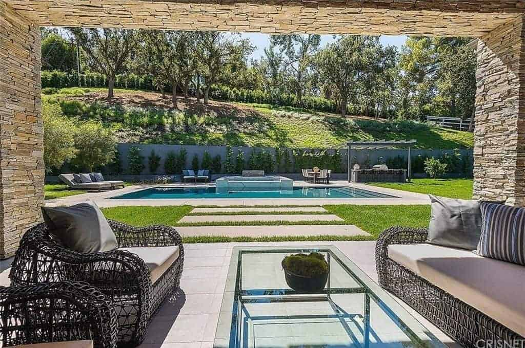 This patio has charming woven wicker sofa and armchairs that have matching beige cushions. This is complemented by a glass-top rectangular coffee table. The real highlight here is the serene view of the pool and amazing landscaping framed with a stone archway.