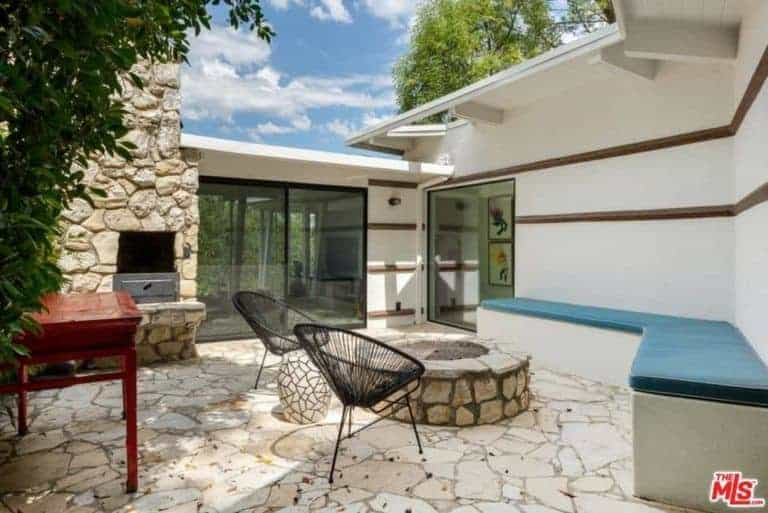 This is a homey patio with a long cushioned bench built-into the wall facing a stone firepit perfect for those impromptu bonfire party. It blends in with the stone flooring and the outdoor fireplace by the large sliding glass doors.