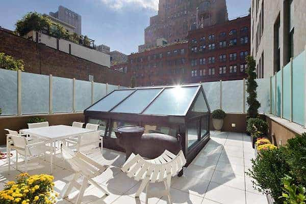 This is a rooftop patio that is surrounded by frosted glass panels for privacy. This is softened by the various potted plants and <a class=