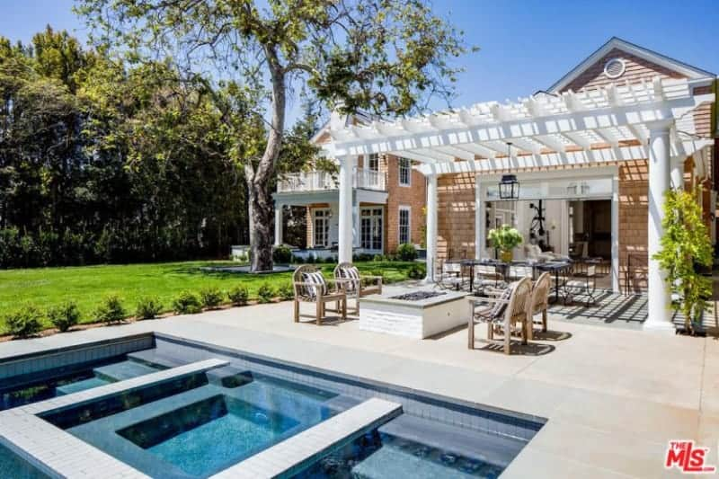 The brilliant white trellis over this patio complements the light hue of the smooth stone flooring that has a white brick firepit jutting out flanked with wooden armchairs with striped pillows beside a geometric pool.
