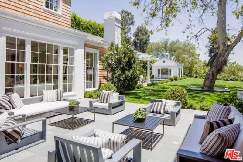 This outdoor patio has a bright demeanor due to its white stone flooring that complements the light gray wooden armchairs benches that have striped pillows to match the couple of coffee table with striped slats on top.