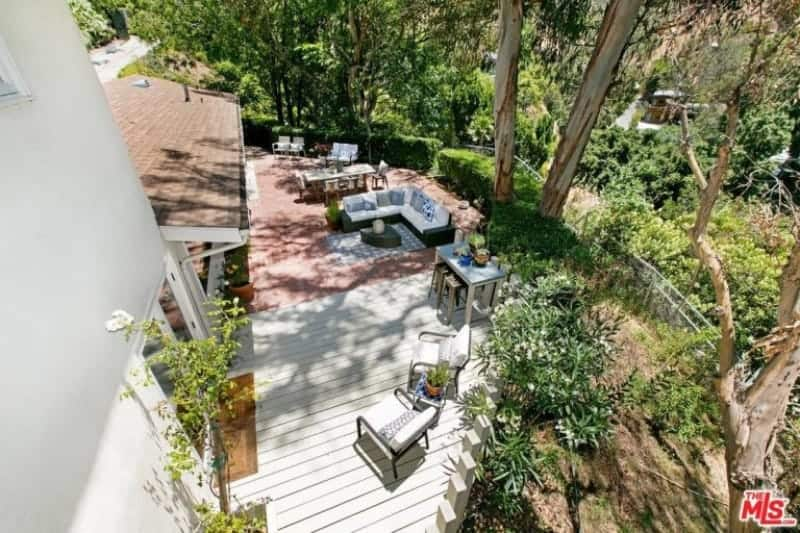 This is large patio beside the house that has two sections surrounded by lush landscaping. One section has white wooden floors with a sitting area of two armchairs. The second section has terracotta flooring under an L-shaped sofa beside a dining area.