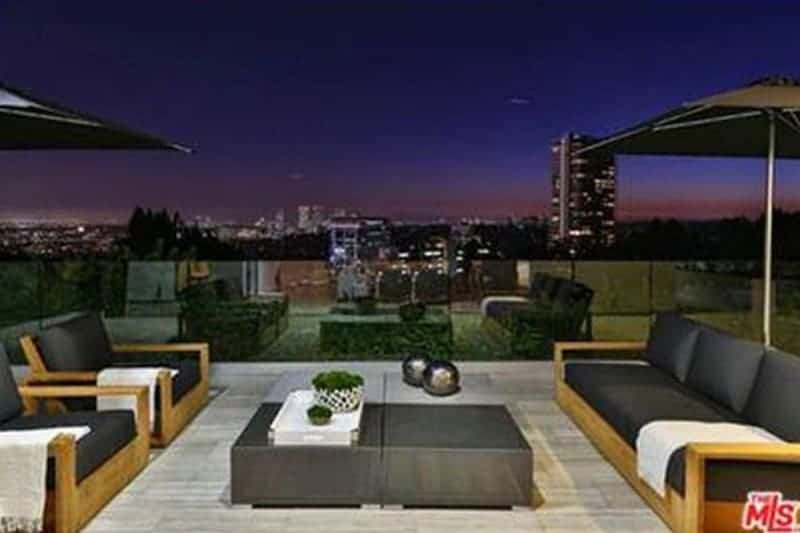 This is a sleek and modern patio that matches with the background of city lights and skyline which is maximized by a low glass. It has matching low wooden armchairs and bench with black cushions matching the low coffee table.