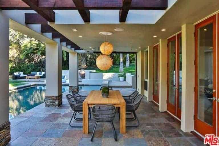 The brilliant spherical pair of pendant lights are the highlight of this outdoor dining area beside the pool with colorful outdoor tiles on the floor and a unique white ceiling framed with exposed beams.