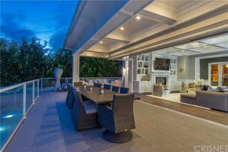 This charming outdoor dining area has woven wicker seats surrounding a long wooden table all with the same chocolate brown hue that complements the light gray flooring and white coffered ceiling.