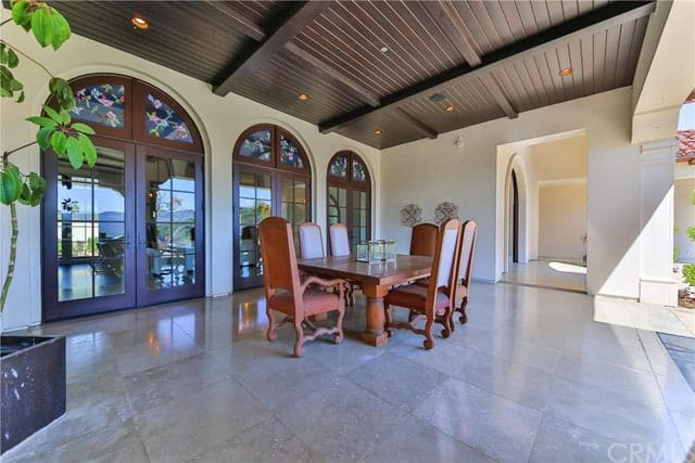 This outdoor dining area has beige marble flooring that matches with the tall walls that are dominated by three arched glass French doors that serves as a nice background for the redwood table and its surrounding chairs.